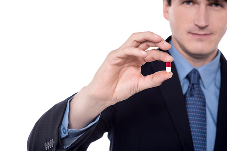 vitamin pill: Cropped image of businessman holding vitamin pill. Stock Photo