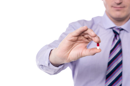 Cropped image corporate executive holding pill.