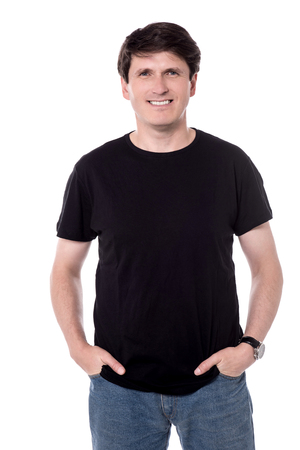 Smiling male with hands in pockets posing to camera. Stock Photo