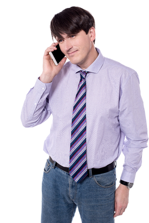 Male executive talking on mobile phone over white.