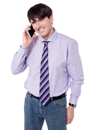 Smiling male executive talking in his  mobile phone.