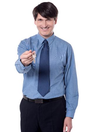 Male house broker giving house key over white. Stock Photo