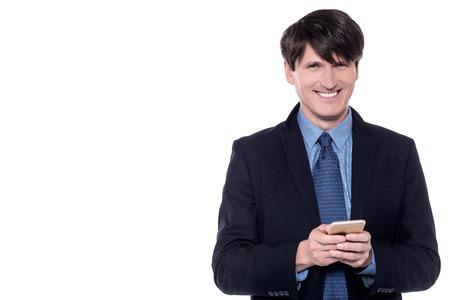 Smiling businessman using his mobile phone.