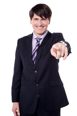 Businessman in suit and tie pointing the finger in front of himself.