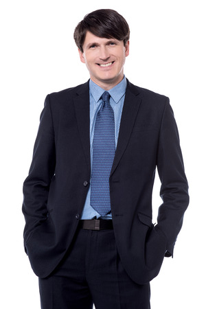 Smart middle aged ceo posing with his hands in pockets.