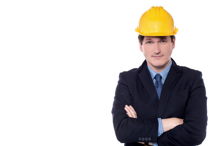 Confident businessman wearing hard hat with folded arms.