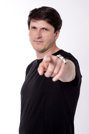 Casual middle aged man pointing finger forward. Stock Photo