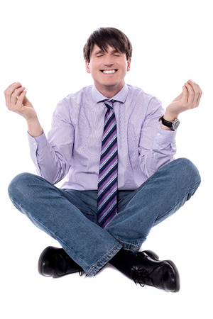 Businessman meditating in lotus position isolated over white. Stock Photo