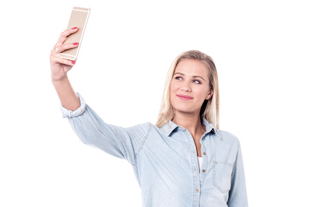 Young woman taking a picture of herself with her camera phone