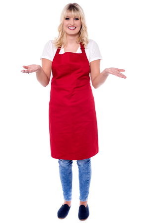 Smiling young female chef with open arms.