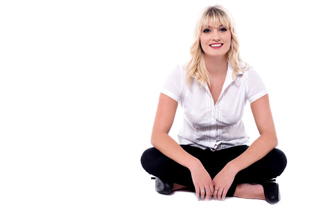 Casual young woman sitting with crossed legs.