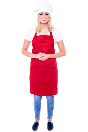 Young female chef posing with her hands clasped.