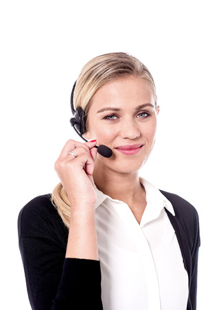 Young female customer support executive adjusting headphones.