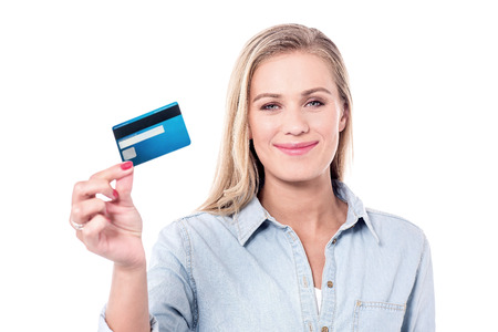 Smiling young woman showing her credit card.