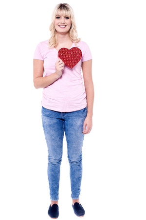 Pretty woman in love holding heart-shaped box.