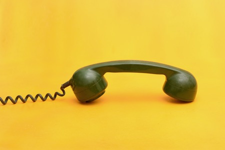 Contact Us concept with old fashioned landline on yellow background