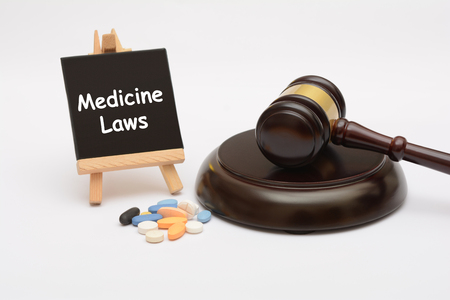 Medicine Law with tablets and gavel on white background
