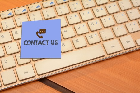 Contact us wrriten on notepad with computer keyboard in background Stock Photo