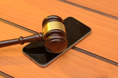 Judge gavel on smartphone, wooden law background