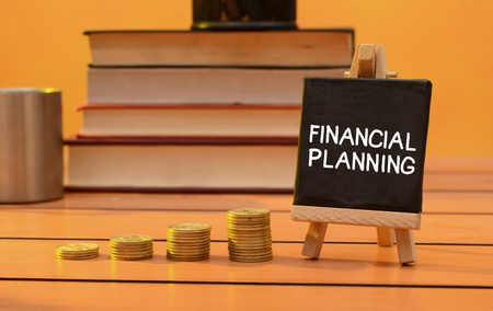 Financial planning concept with coins pile and books Фото со стока