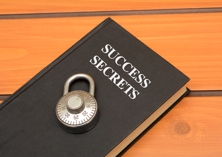 Success secrets concept with book on wooden background