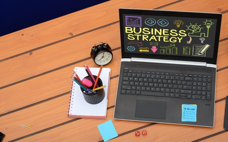 Business strategy text on laptop screen, Business concept on wooden background