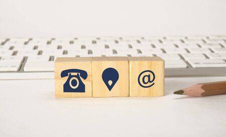 Contact icons on wooden blocks with keyboard, Contact Us concept