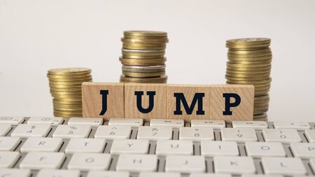 Text of Jump on wooden blocks with coin stack, small to big concept Foto de archivo