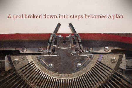 Old manual typewriter typed text of a goal broken down into steps becomes a plan