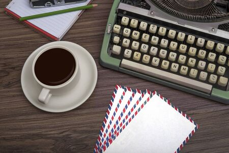 Typewriter on the old wooden desk with coffee cup and note book top view