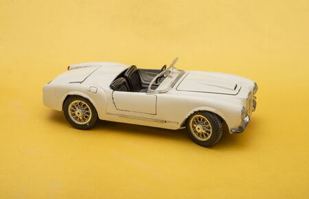 White retro car toy model isolated on yellow background, transportation concept