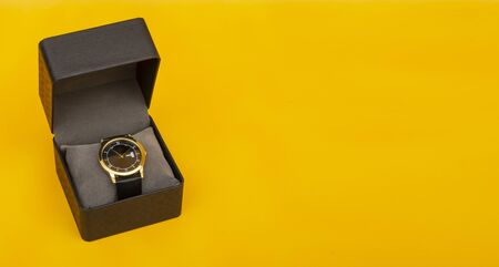 Luxury style golden hand watch in gift box on yellow background with copy space