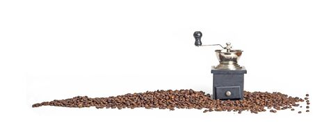 Close up photo of coffee beans with grinder on white background.