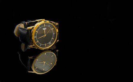 Goldene Wrestwatch im Luxusstil auf schwarzem Tuch Nahaufnahme. Standard-Bild