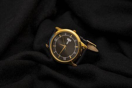 Goldene Handuhr im Luxusstil auf schwarzem Stoff mit Geschäftszeitenkonzept. Standard-Bild