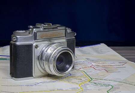 Close up vintage film camera on map with copy space, travelling concept