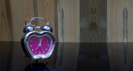 Love heart shaped table clock on wooden background with copy space Stock fotó
