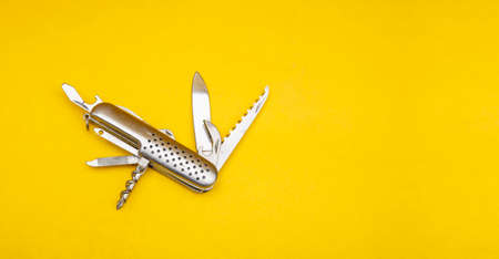Close up photo of multifunction knife on yellow background with copy space