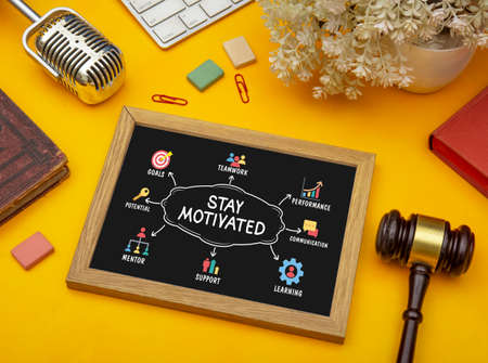 Stay motivated infographic on slate in office table top view