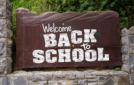 Wooden sign outside a school welcoming back the students after covid-19
