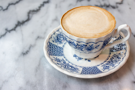 Coffee milk in a cup, rose patterned ceramic cup, on marble table in the morning light.