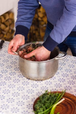 Man is stirring minced meat in a metal pan in the kitchen. Photo set