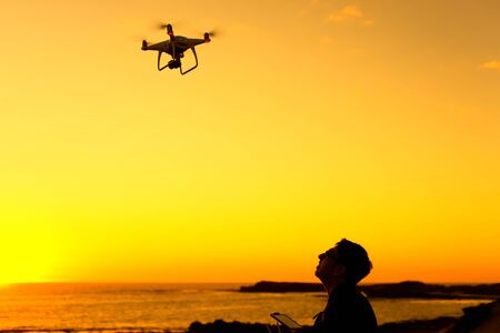 A silhouette of a man looking on a drone in sunset. Stock Photo