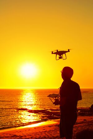 A photo of a man flying his drone on a beach in sunset. Vertical orientaton. Stock Photo