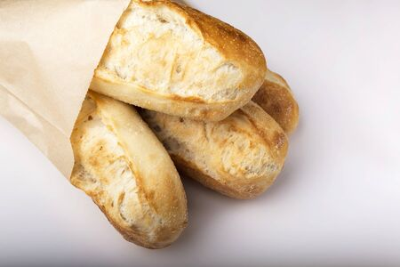 French baguettes in paper bag isolated on light background.