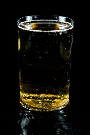 Glass of cold beer with foam on  black background photo