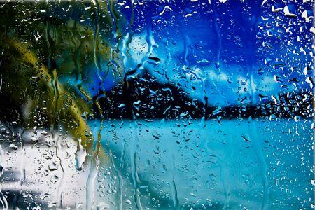 Sea and palm through wet window photo