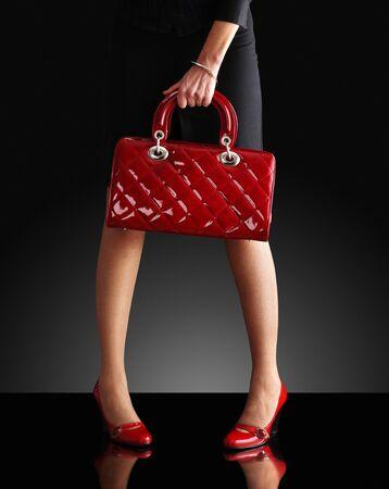leren tas: modieuze vrouw met een rode tas, alleen de benen