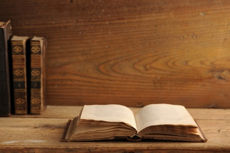 OLD LIBRARY: old book open on a wooden table Stock Photo