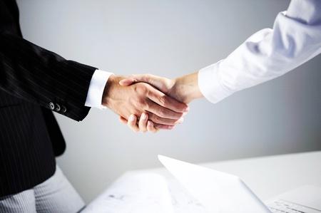 d'affaires: Femme et shakinghand les hommes dans le bureau